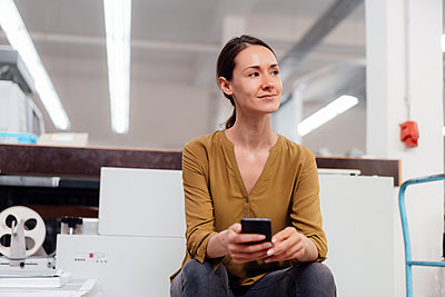 Thoughtful businesswoman with smart phone sitting in workshop - p300m2299365 by Kniel Synnatzschke