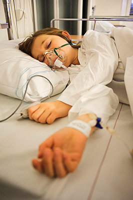 Girl lying on hospital bed with oxygen mask over face - p31228875 by Hans Berggren