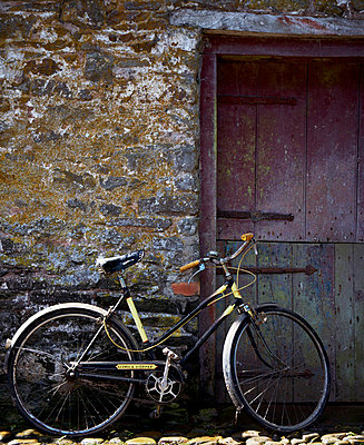 Bicycle leans on wall near stable door - p349m789676 by Brent Darby