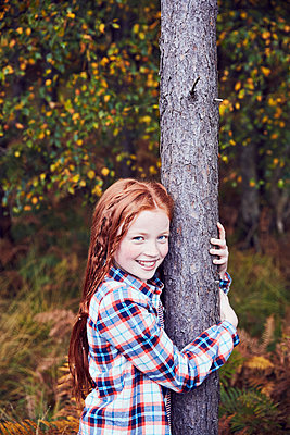 Portrait of young girl, hugging tree, smiling - p429m1407741 by Emma Kim