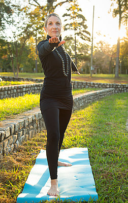 Caucasian woman practicing yoga in park - p555m1219422 by WHL
