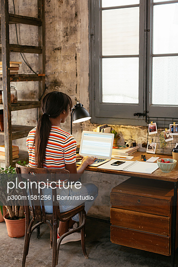 Back view of young woman sitting at desk in a loft working on laptop - p300m1581256 by Bonninstudio