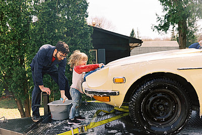 A father and his children washing a classic car together. - p1166m2190654 by Cavan Images