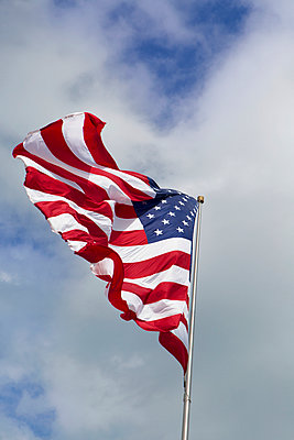 Low angle view of American flag against cloudy sky - p1166m969291f by Cavan Images