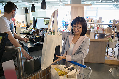 Smiling senior woman placing reusable bags in shopping cart at grocery store checkout - p1192m1567211 by Hero Images