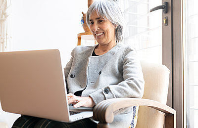 Smiling woman using laptop while sitting on armchair at home - p300m2275204 by Jose Carlos Ichiro