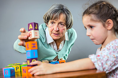 Senior woman stacking toy block while playing with girl at home - p300m2287548 by Stefanie Aumiller