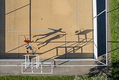 Male and female athletes jumping while playing basketball - p300m2299962 by Stefan Schurr