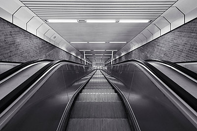 Black and white of descending escalator - p301m2018515 by Norman Posselt