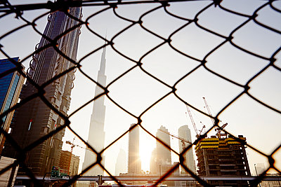 Skyscrapers, chain-link fence on background - p312m1024781f by Magnus Ragnvid