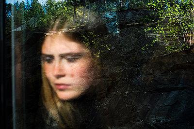 Portrait of young woman through glass - p352m2119789 by Lena Katarina Johansson
