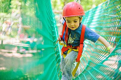 Caucasian boy in harness climbing on net - p555m1411204 by Alberto Guglielmi