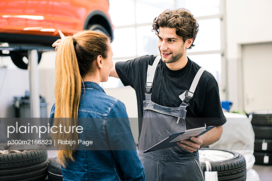 Car mechanic talking to client in workshop - p300m2166823 by Robijn Page