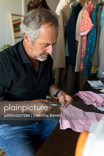 Mature tailor working at table in studio - p300m2227284 by Valentina Barreto