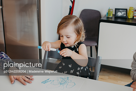 Girl sitting at table and holding pen - p312m2208204 by Madeleine Wejlerud