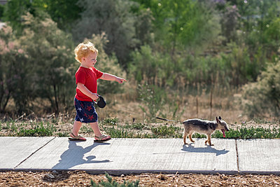 Side view of cute baby boy pointing while walking with puppy on footpath in park - p1166m2067852 by Cavan Images