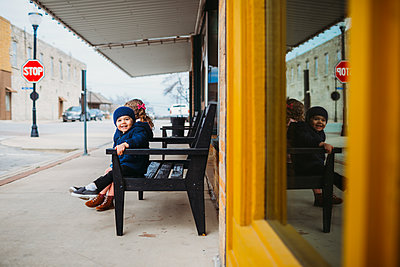 Young boy smiling while sitting on bench with young girl - p1166m2124379 by Cavan Images