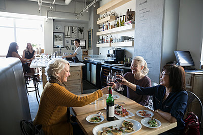 Active senior women friends toasting wine glasses, celebrating in cafe - p1192m1567175 by Hero Images