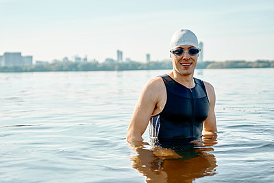 Young athlete in swimming goggles and cap looking at side - p1630m2196903 by Sergey Mironov