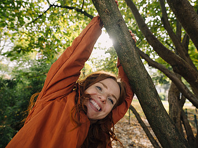 Happy redheaded woman enjoying autumn in a park - p300m2167253 by Kniel Synnatzschke