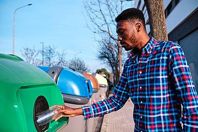 Mid adult man putting glass jar in recycling bin on footpath - p300m2273544 by Alvaro Gonzalez