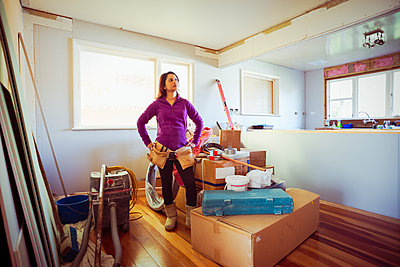 Mixed race woman surveying remodeling project - p555m1411050 by Donald Iain Smith