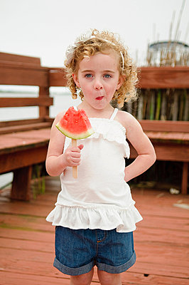 Girl eating watermelon - p924m711064f by Matt Dutile