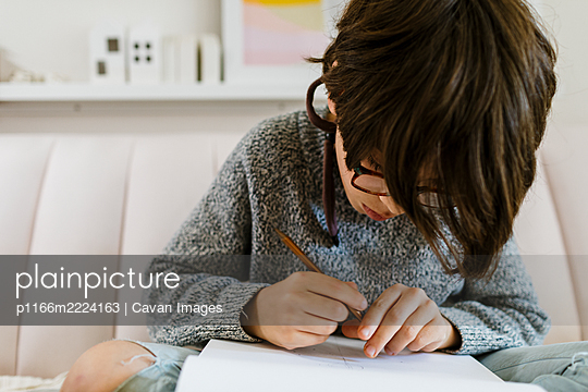 Cropped view of boy hands sketch book and mechanical pencil on sofa - p1166m2224163 by Cavan Images