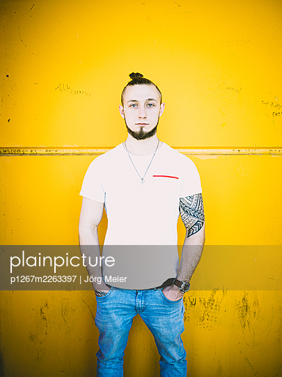 Man with tattoo and pigtail against yellow wall - p1267m2263397 by Jörg Meier
