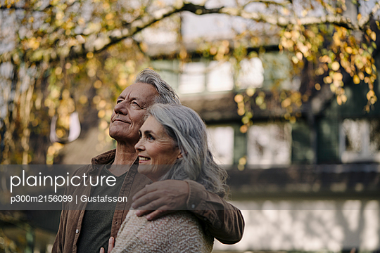 Affectionate senior couple in garden of their home in autumn - p300m2156099 by Gustafsson