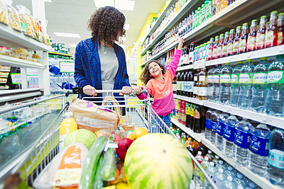 Mother and daughter shopping in supermarket - p1023m2187649 by Robert Daly