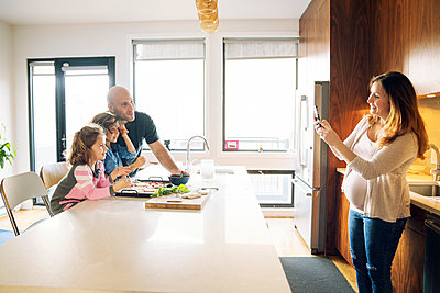 Pregnant woman photographing family at kitchen counter in home - p1166m1210349 by Cavan Images