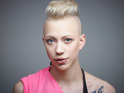 Portrait of young woman with tattoos against grey background, smiling - p300m1174673 by Rainer Holz