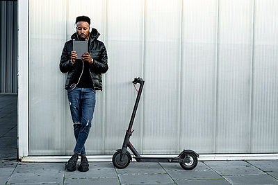 Man with headphones, tablet and e-scooter outdoors - p300m2167498 by Rafa Cortés