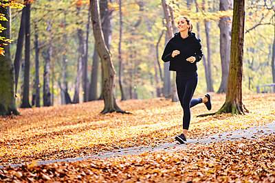 Young woman jogging in autumn forest - p300m2213931 by Bartek Szewczyk