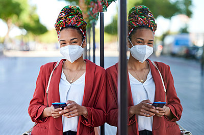 Spain, Andalusia, Jerez, woman with mask and headscarf using mobile phone in the street. - p300m2266965 von Kiko Jimenez