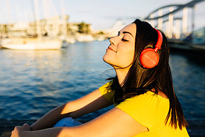 Young woman listening music through headphones while sitting by sea - p300m2293961 by Xavier Lorenzo