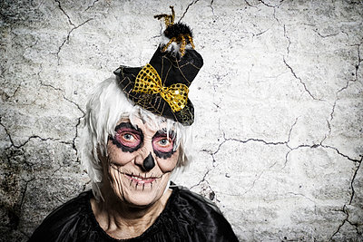 Portrait of senior woman with sugar skull make-up and fancy hat - p300m973773 by Stefanie Baum
