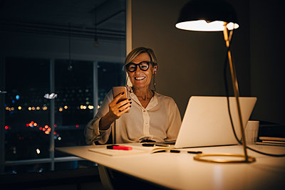 Smiling businesswoman using smart phone while sitting with laptop at illuminated desk in coworking space - p426m2194764 by Maskot