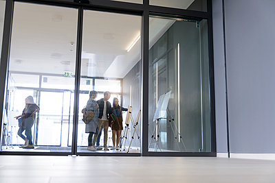 Students in college building reading notice board by glass doors - p429m2018850 by suedhang photography