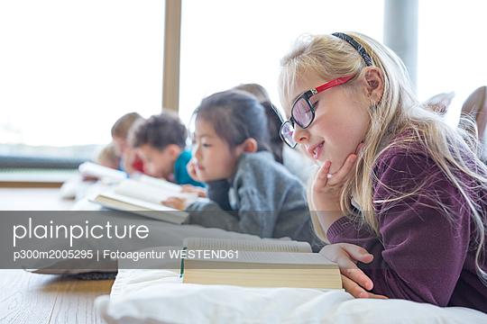 Pupils lying on the floor reading books in school break room - p300m2005295 von Fotoagentur WESTEND61