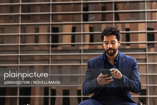 Male business person using smart phone in city - p300m2227096 by NOVELLIMAGE