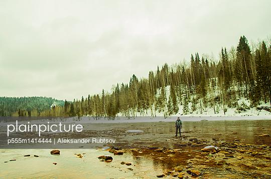 Caucasian hiker standing in rocky remote river - p555m1414444 by Aleksander Rubtsov