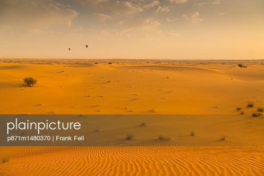 Hot air balloons over sand dunes at sunrise in the Dubai Desert, Dubai, United Arab Emirates, Middle East - p871m1480370 by Frank Fell