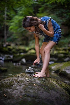 Girl stacking stones on the riverbank - p1007m2220013 by Tilby Vattard