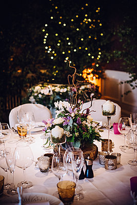 A table laid for a special occasion, with a floral centrepiece and candles, at night.  - p1100m1080169f by Mint Images