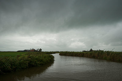 Dark clouds over Friesland canal - p1132m1492421 by Mischa Keijser
