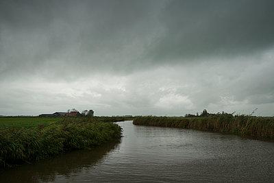 Graue Wolken über einem Kanal in Friesland - p1132m1492421 von Mischa Keijser