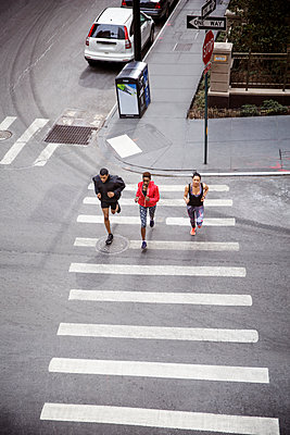 Overhead view of athletes running on zebra crossing on city street - p1166m1145139 by Cavan Images