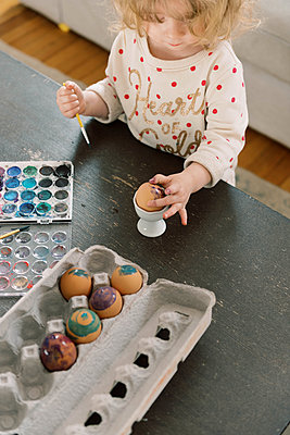 Little toddler girl painting eggs with watercolors for Easter. - p1166m2152335 by Cavan Images